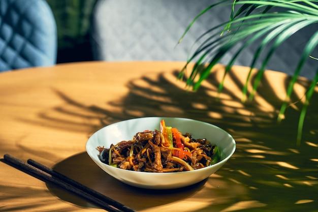 白いボウルに鍋野菜を入れた甘酸っぱい豚肉。中華料理。