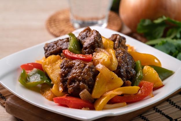 Жареные во фритюре свиные ребрышки в кисло-сладком соусе с нарезанным перцем и ананасом в тарелке на деревянном столе