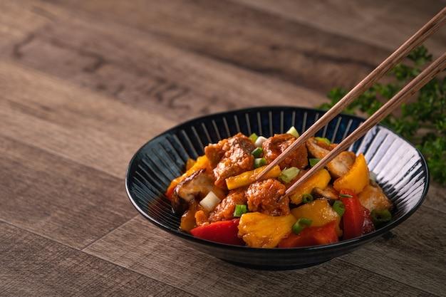 Жареная во фритюре свинина в кисло-сладком соусе с нарезанным перцем и ананасом в синей тарелке на деревянном столе
