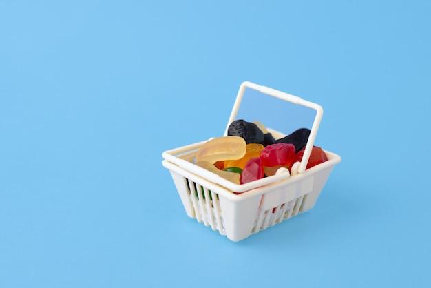 甘くておいしいキャンディー-マーマレード、ゼリーキャンディー、おもちゃのフードバスケット、テキスト用のスペースのある青い表面のショッピングトロリー。