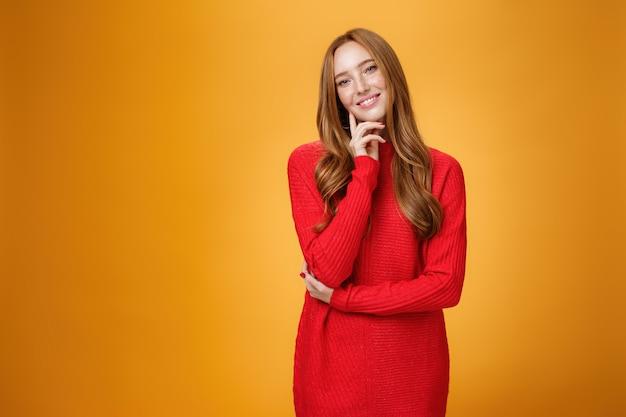 赤いニットのドレスでかわいいそばかすのある甘くて優しい赤毛の女性は、指で顔に触れて、オレンジ色の背景の上にカメラを愛して喜んで笑って頭を傾けます