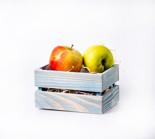 Sweet apples in wooden crate, isolated on white