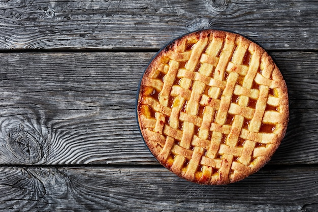 어두운 소박한 나무 테이블, 평평한 평지, 여유 공간에 검은 접시에 격자 파이 크러스트 토핑이있는 달콤한 살구 shortcrust 파이