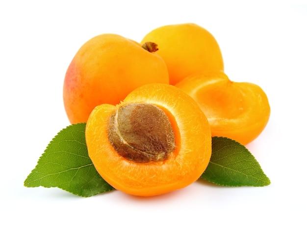 Сладкие плоды абрикоса с листьями на белом
