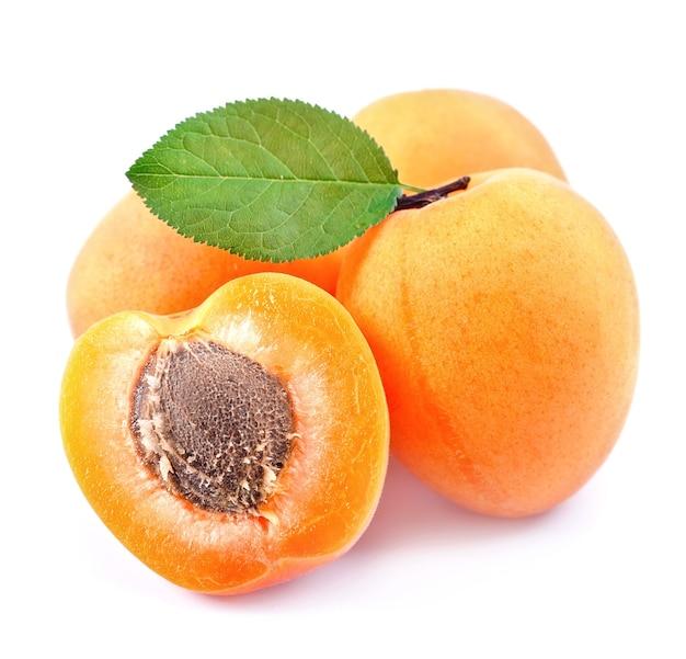 Сладкие абрикосы с листьями, изолированными на белом