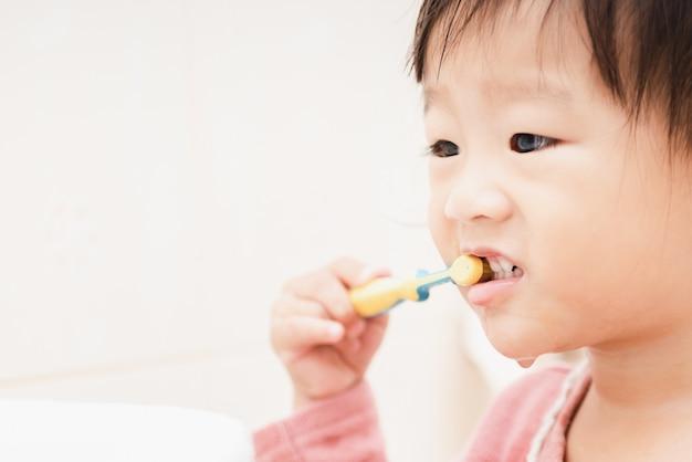 Sweet asian child little girl brushing her teeth in bathroom