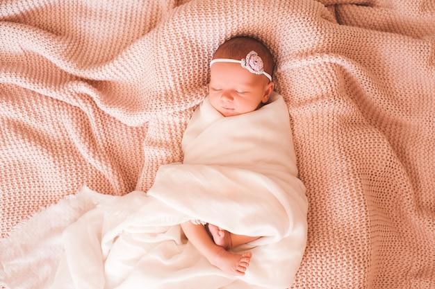 ベッドのクローズアップで眠っている甘い女の赤ちゃん