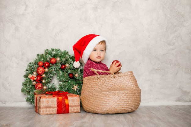 Sweet baby santa sits in a wicker basket with a gift box