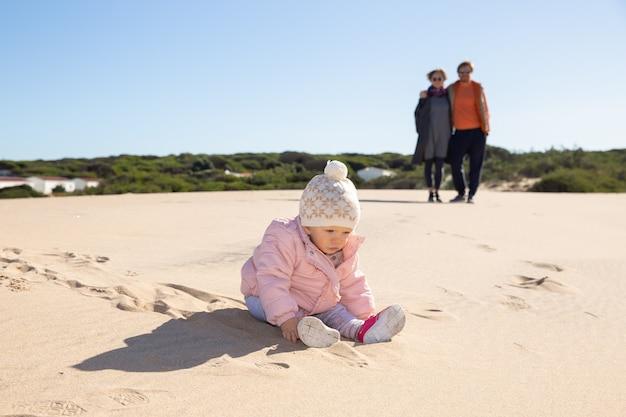 ピンクのジャケットと帽子をかぶって、屋外の砂で遊ぶ甘い赤ちゃん