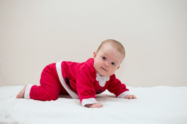 Sweet baby wearing santa costume over sheetbed