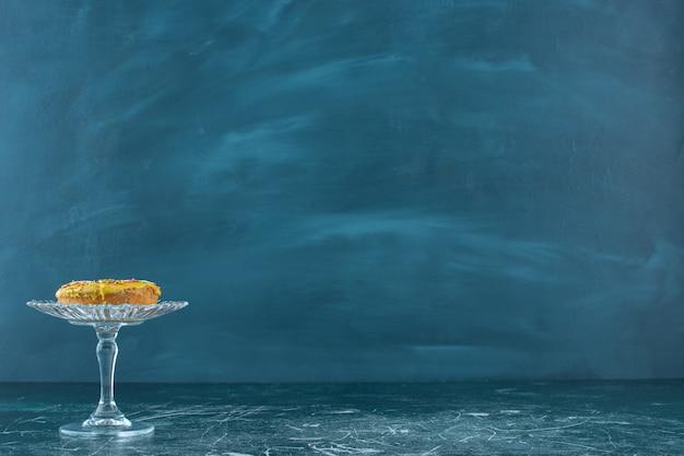 Bagel dolce ricoperto di gocce di cioccolato su un piedistallo di vetro, sullo sfondo blu. foto di alta qualità