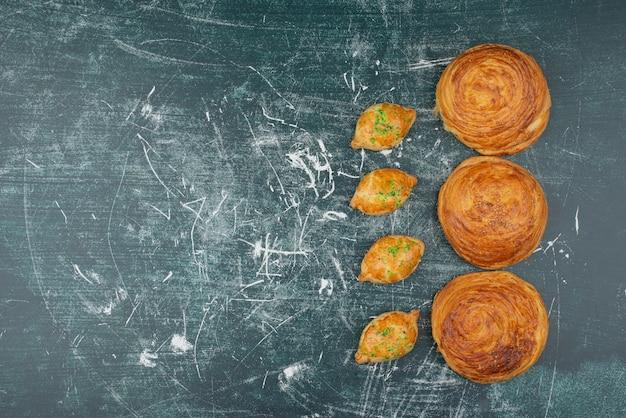 大理石のテーブルの上の甘いパン屋とgoglas。