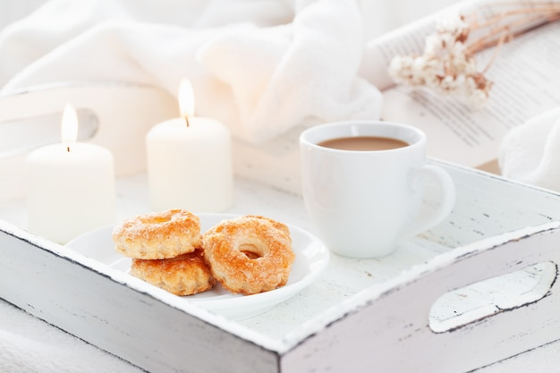 Sweet bakery with cup of coffee on white wooden shabby chic tray with burning candles and open book.