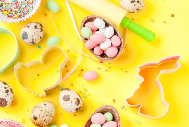 Sweet baking concept for easter cooking background with baking - with a rolling pin whisk for whipping cookie cutters quail eggs sugar sprinkling
