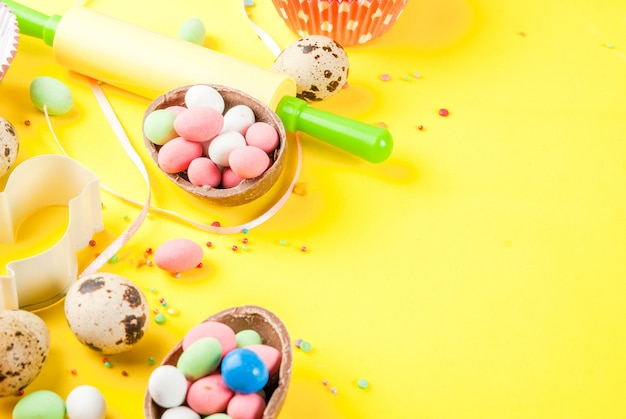 Sweet baking concept for easter, cooking  with baking - with a rolling pin, whisk for whipping, cookie cutters, quail eggs, sugar sprinkling. bright yellow  , top view  copyspace