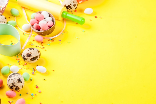 Sweet baking  for easter, cooking  with baking  with a rolling pin, whisk for whipping, cookie cutters, quail eggs, sugar sprinkling. bright yellow , copyspace