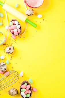 Sweet baking  for easter, cooking  with baking  with a rolling pin, whisk for whipping, cookie cutters, quail eggs, sugar sprinkling. bright yellow ,  top view