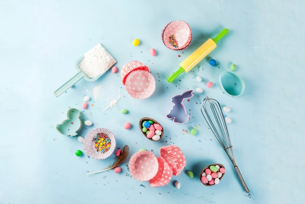Sweet baking  for easter,  cooking  with baking  with a rolling pin, whisk for whipping, cookie cutters, sugar sprinkling, flour. light blue background, top view