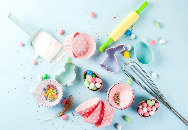 Sweet baking  for easter,  cooking  with baking  with a rolling pin, whisk for whipping, cookie cutters, sugar sprinkling, flour. light blue , top view copyspace