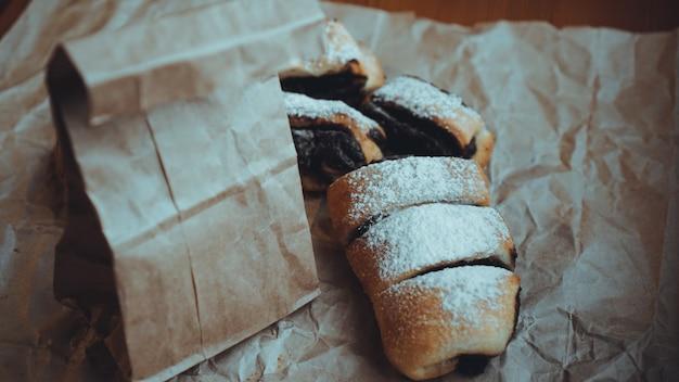 クラフト紙の甘いベーキング製品。食べ物の写真。甘いペストリー。ベーカリーショップのバナー。レシピ本の写真。配達用紙袋
