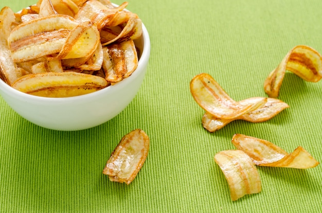 Sweet banana chips on green tablecloth
