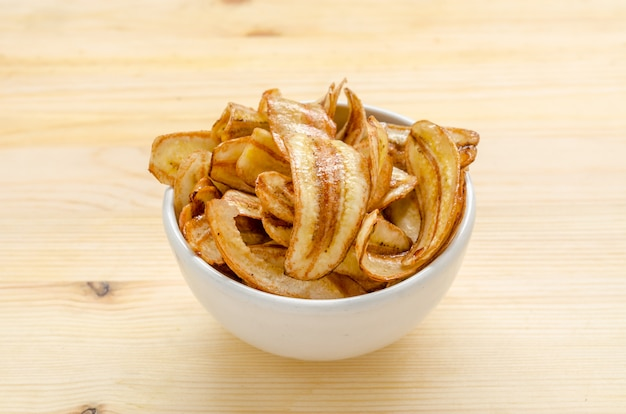 Sweet banana chips on wooden table