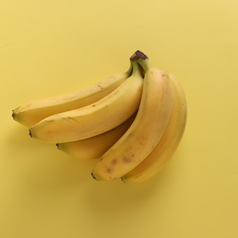 Sweet bananas on punchy pastel yellow background, top view, closeup