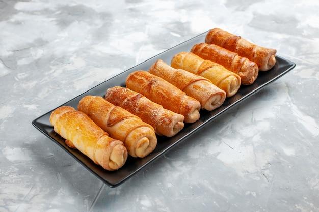 Sweet bangles baked filled pastries inside black mold on light desk