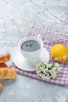 軽い机の上にコーヒーとレモンと一緒に詰め物と甘い腕輪