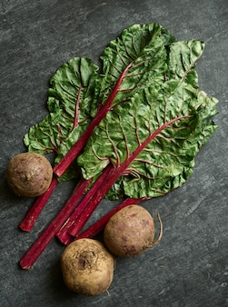 Sweet beet and leaves close up, chard, gray table