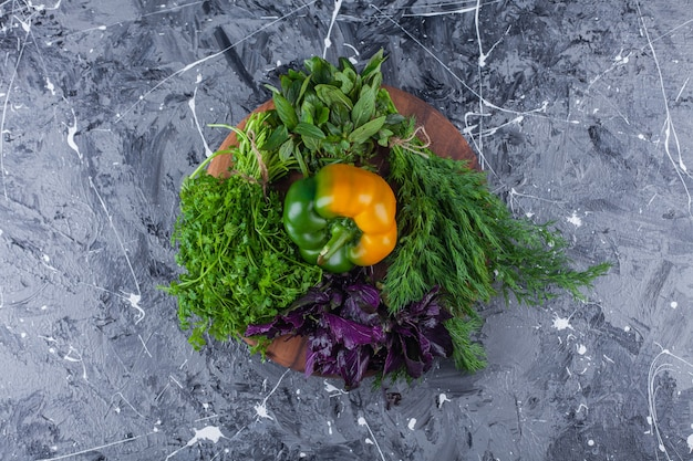Sweet bell pepper with dill and basil in clay bowl.