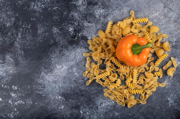 Сладкий болгарский перец с сухой сырой пастой на мраморе.