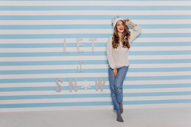Милая, доброжелательная девушка с длинной роскошной прической радостно улыбается на полосатой стене. портрет европейской модели в зимней шапке в полный рост