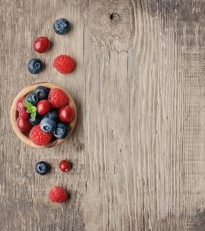 Сладкая ягодная смесь на деревянном столе. спелая малина и черника.