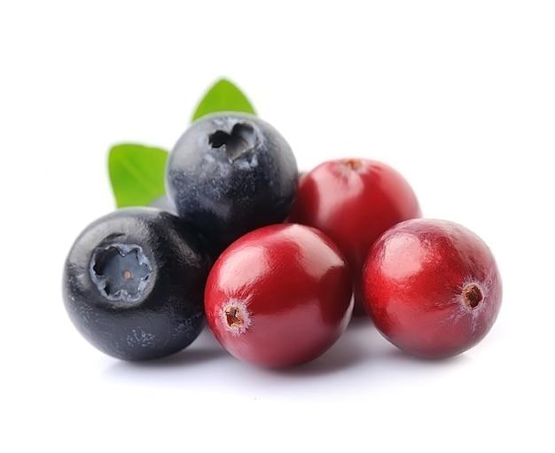 Сладкие ягоды клюквы и черники, изолированные на белом фоне