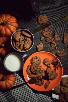 Sweet biscuit cookies dessert and milk with halloween holiday dinner prop decoration with wood table
