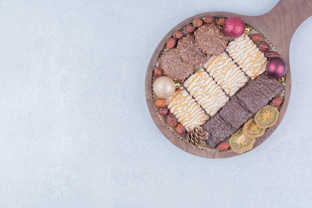 Biscotti dolci e palle di natale su tavola di legno.