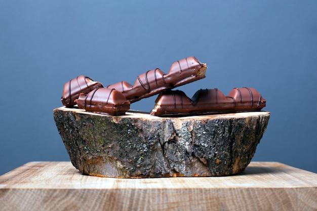 甘いブラックチョコレートと灰色の背景に装飾的なフォレストボード。木製のスタンドに壊れたキャンディー。 。