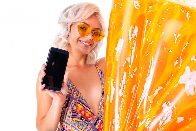 Sweet blonde girl in a swimsuit in sunglasses holds a phone with mockup with a swimming circle pineapple