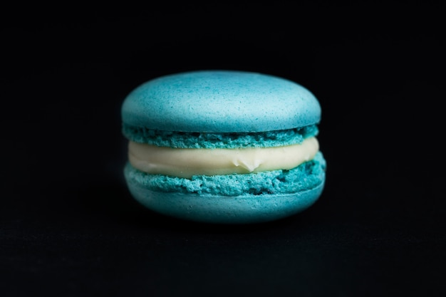 黒の背景に分離された甘い青いマカロン