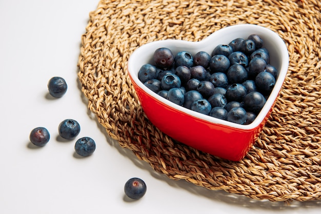 Sweet blueberries in a plate in the shape of heart on a white and wicker placemat background. high angle view.