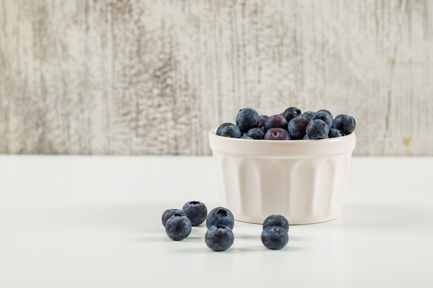 Sweet blueberries in a white bowl side view on a grunge and white background