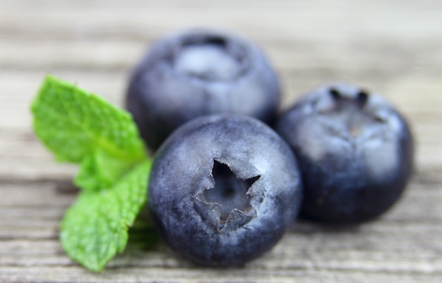 Sweet blueberry with leafs on the wooden texture