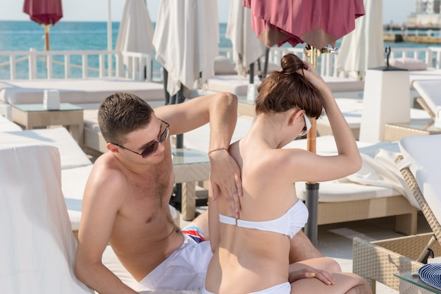 Sweet boyfriend helping his girlfriend putting sunscreen lotion on her back while sitting on the lounge chair in the resort.