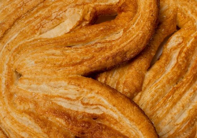 Сладкая плетеная предпосылка текстуры печенья palmiers, сердце ладони или образец уха слона. французское слоеное тесто или паштет feuilletee вид сверху