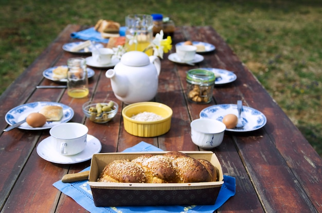 Sweet bread and breakfast food on wooden table in the home yard.