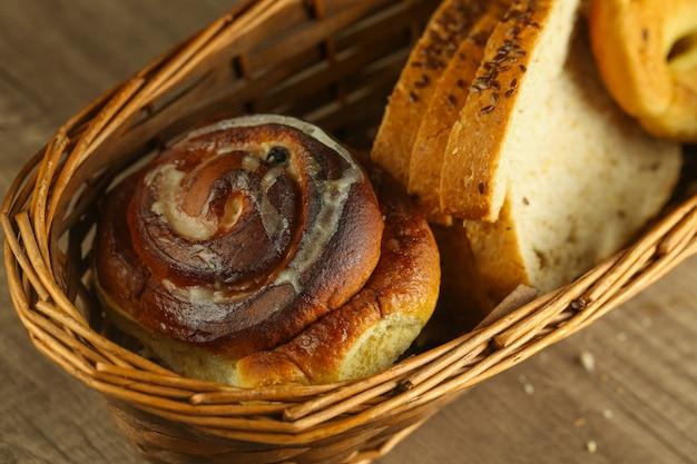テーブルの上の枝編み細工品バスケットの甘いパン
