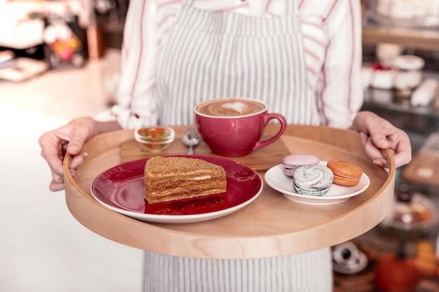 甘い朝食。トレイの上に立っているおいしいケーキとおいしいマカロンのクローズアップ