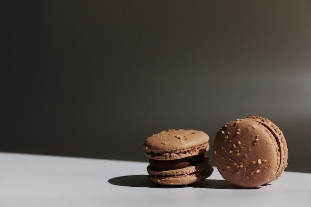 窓からの光線で白い背景に分離された甘い茶色のチョコレートフレンチマカロンまたはマカロンデザート。