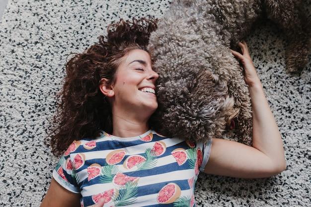 Сладкая коричневая испанская водяная собака играет с ее владельцем и лижет ее лицо. наслаждаясь прекрасным временем вместе. стиль жизни дома, любовь